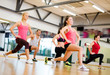 group of smiling people exercising in the gym - 58752503