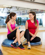 two smiling women sitting on the half balls