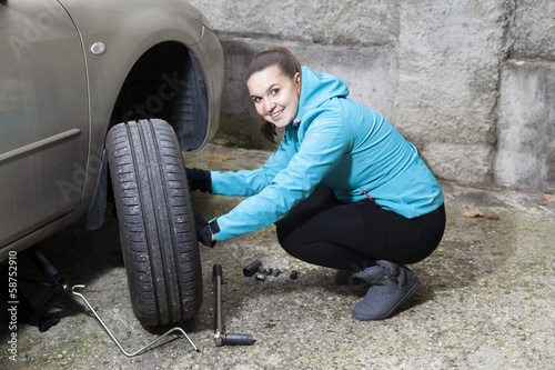 Young woman driver changes car tyres