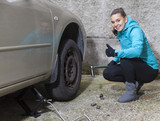 Young smiling woman driver replacing tires, showing OK sign