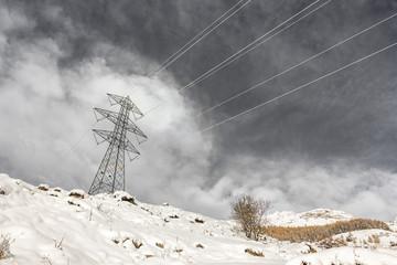 Traliccio della corrente in montagna con neve