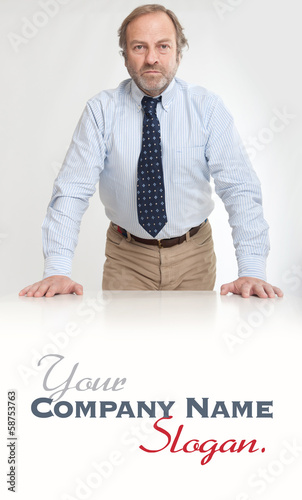 Serious man leaning on a desk