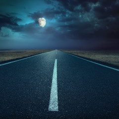 Driving on asphalt road at night towards the moon