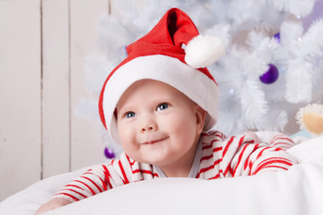 Smiling baby boy in Santa`s hat under the Christmas tree