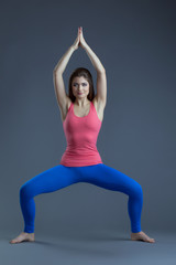 Image of charming young yoga trainer shows asana