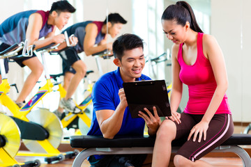 Asian personal trainer with woman in fitness gym