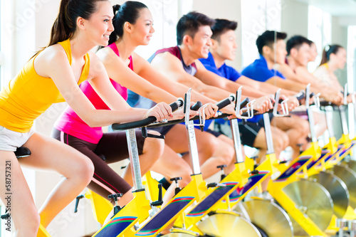 Asian people in spinning bike training at fitness gym