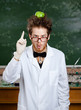 Crazy scientist with a green apple on his head shows forefinger