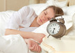 sleeping woman resting in bed with alarm clock