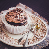 Beautiful chocolate cupcake on vintage plate.