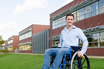 junger lächelnder Mann im Rollstuhl