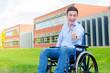 glücklicher Rollstuhlfahrer zeigt Daumen