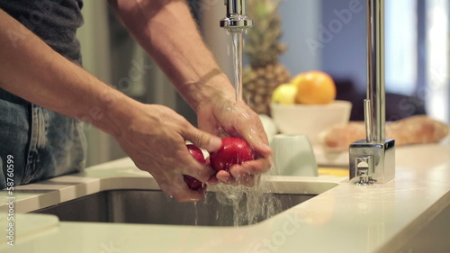 Man washing tomato under tap water