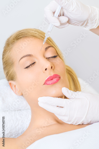 Young woman receiving botox injection in lips