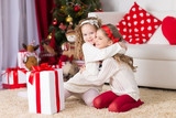 two adorable curly girls playing with gift box