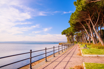 Promenade and pine trees in Bolsena lake, Italy.