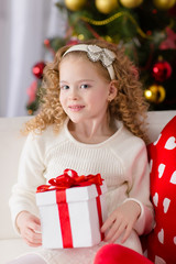 Portrait of  smiling cute girl with Christmas gift