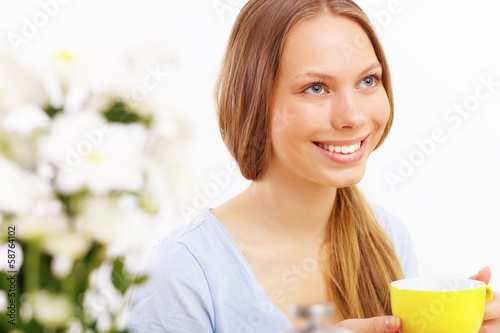 Beautiful young woman drinking tea