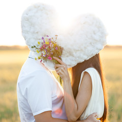 Young couple kissing behind
