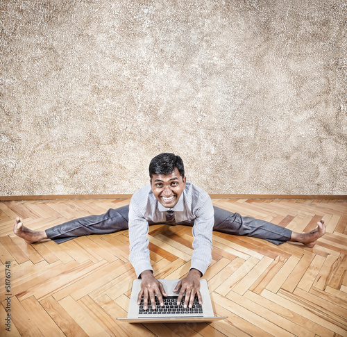 Indian man doing yoga with laptop