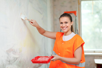 painter paints wall with brush