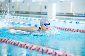 Young girl in goggles swimming butterfly stroke style