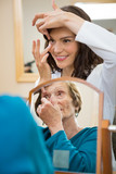 Eyecare Doctor Teaching Senior Woman To Insert Contact Lens