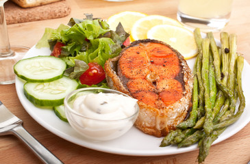 salmon served with vegetable salad, asparagus, lemon and sauce