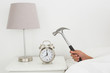 Hand smashing alarm clock with hammer in bed