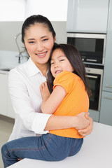 Portrait of a mother carrying her young daughter in kitchen