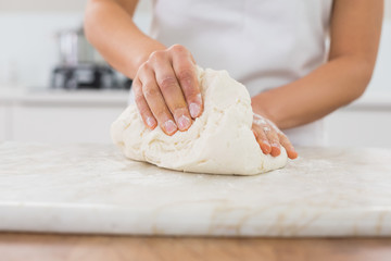 Mid section of a woman kneading dough in kitchen