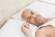 Close-up of a smiling mature man resting in bed