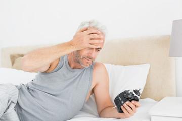 Man looking at alarm clock in bed