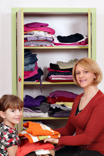 mother and daughter agrees clothes in a closet