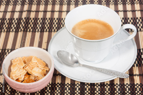 a cup of coffee with almond cookie on bamboo mat