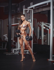 Sexy athlete girl in bikini with a dumbbells in the gym