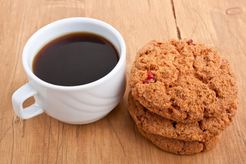 pile of cookies and a cup of coffee on a wooden table