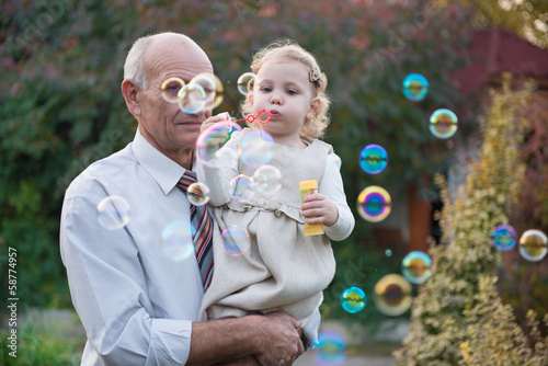 Cute infant blowing soap bubbles