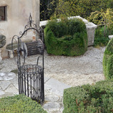 ancient well in the cured Italian-style garden of a villa