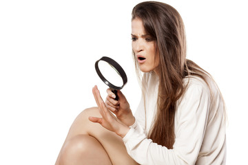 shocked young woman looking through a magnifying glass her nails