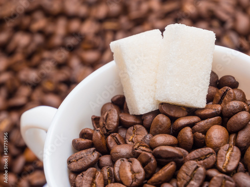 Coffee beans in a cup with pieces of sugar