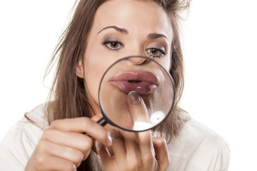 young woman checks her lips through the magnifying glass