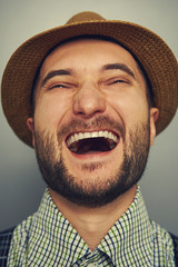 laughing hipster man over grey