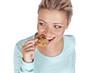 Hübsche junge Frau ißt einen Keks