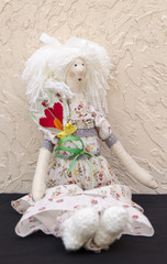 Handmade doll with a flower in his belt in a long white dress si