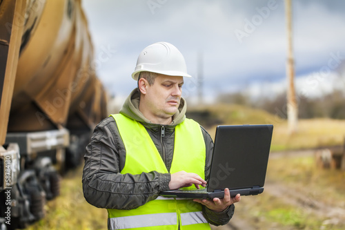 Railroad employee with PC near the tank wagons