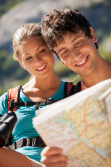 Closeup of couple in the mountains looking at the map