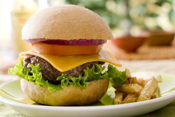Closeup of a burger with fries.