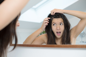 Horrified young woman looking in the mirror