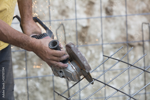 Construction site worker grinding armature